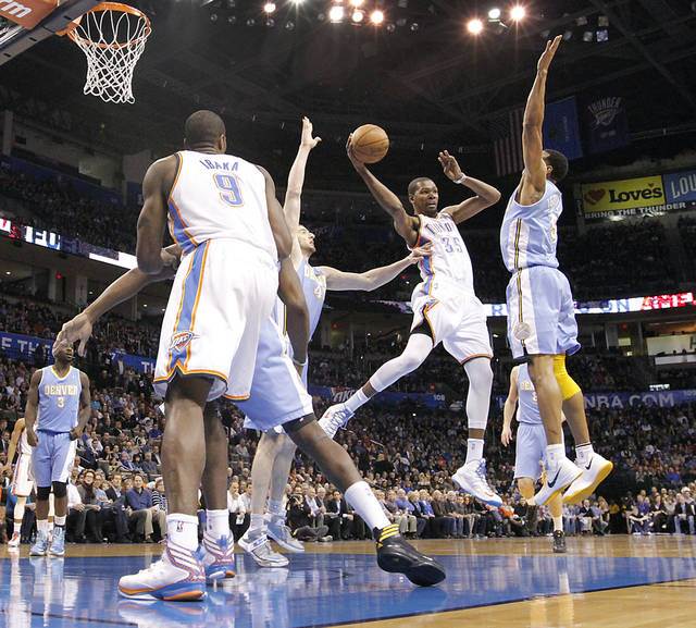Oklahoma City's Kevin Durant (35) passes the ball past Denver's Andre Iguodala (9) during the NBA basketball game between the Oklahoma City Thunder and the Denver Nuggets at the Chesapeake Energy Arena on Wednesday, Jan. 16, 2013, in Oklahoma City, Okla.  Photo by Chris Landsberger, The Oklahoman