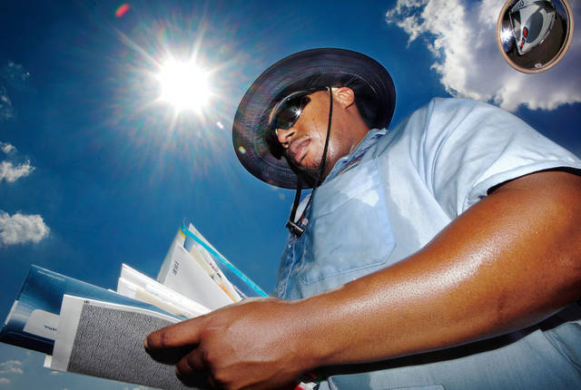 Oklahoma City  set a new heat record when temperatures  topped the the century mark Monday afternoon, Aug. 22, making it the 51st day in 2011 when the temperature exceeded 100 degrees.  Letter carrier Anthony Belton sorts mail near his truck  before delivering the mail to homes in the 600 block on NW 92 on Monday. A mailman for five years, he said he tolerates working in the heat by wearing a wide-brimmed hat, shorts and drinking lots of water. He lifted his hat to reveal about a dozen ice cubes inside it.     by Jim Beckel, The Oklahoman