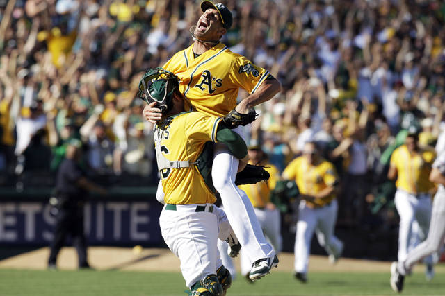 Oakland Athletics relief pitcher Grant Balfour, top, and catcher Derek Norris celebrate after their 12-5 win over the Texas Rangers in a baseball game, Wednesday, Oct. 3, 2012 in Oakland, Calif. The A's clinch the AL West title with the win. (AP Photo/Ben Margot)