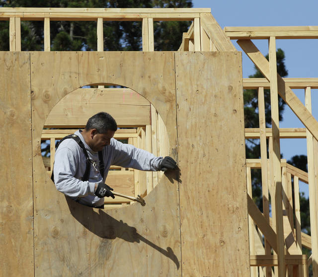 Mario Sanchez works on a new home in Palo Alto, Calif. Confidence among builders hit a five-year high in June.  AP Photo