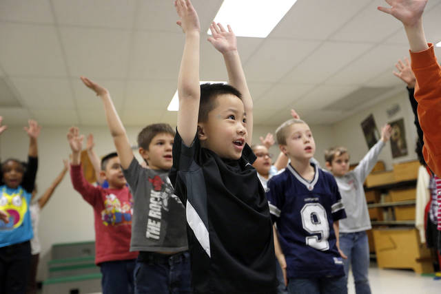 Right: First-grader Brian Bui practices during Christy Gosset�s music class for a musical program at  Western Oaks Elementary.