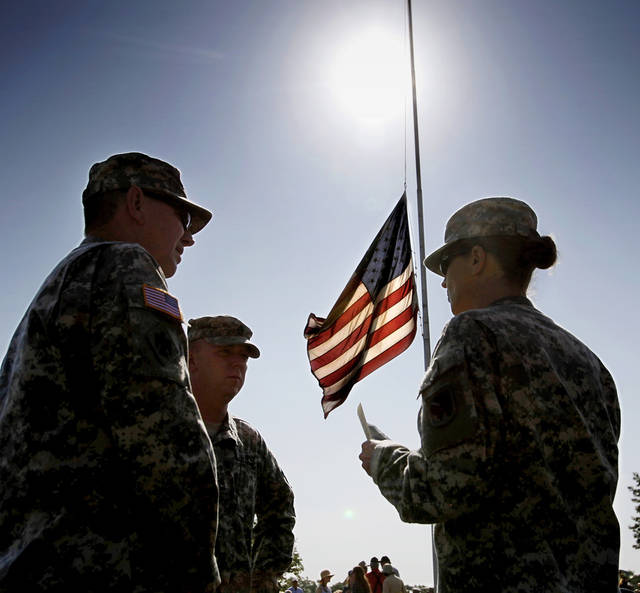 Three soldiers from the Oklahoma Army National Guard talk beneath an American flag being flown at half-staff before the start of  the Memorial Day Ceremony on the grounds of the 45th Infantry Division Museum  on Monday,  May 28,  2012,  Photo by Jim Beckel, The Oklahoman