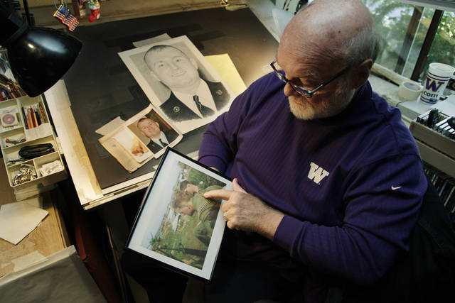 Artist Michael Reagan holds a photo of himself as a Marine in Vietnam in 1967 as he works at his drawing table on a portrait of Joseph A. Weems, who died after being after being hit by a train while riding his bicycle near the Ramstein Air Base in Germany as he served in the U.S. Air Force, Thursday, Oct. 4, 2012 at his home in Edmonds, Wash. Since starting the Fallen Heros Project in 2004, Reagan has drawn more than 3,000 portraits and given them free-of-charge to families of fallen soldiers. (AP Photo/Ted S. Warren)