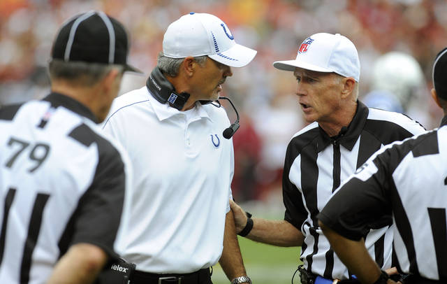 Indianapolis Colts coach Chuck Pagano, center left, talk with referee Jerry Hughes, right, during the first half of an NFL preseason football game against the Washington Redskins on Saturday, Aug. 25, 2012, in Landover, Md. (AP Photo/Richard Lipski)