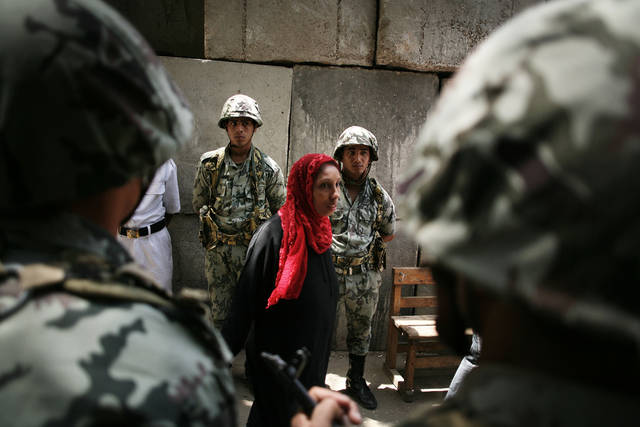 A woman leaves the polling station as Egyptian military soldiers stand guard in front of a polling center in downtown Cairo, Egypt, Thursday, May 24, 2012. In a wide-open race that will define the nation's future political course, Egyptians voted Thursday on the second day of a landmark presidential election that will produce a successor to longtime authoritarian ruler Hosni Mubarak. (AP Photo/Manu Brabo)