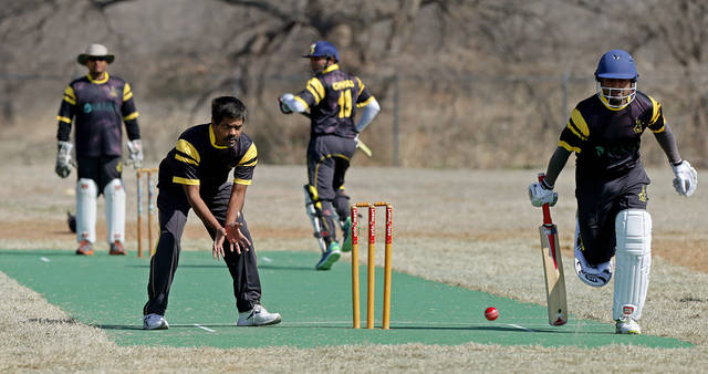 Batsman Rey Ganadeep, at right, runs as bowler Jagan Patlolla waits for the ball during the Oklahoma City Strikers Cricket Club's first game on its new field at Douglass Park in Oklahoma City, Saturday, March 29, 2014. Photo by Bryan Terry, the Oklahoman
