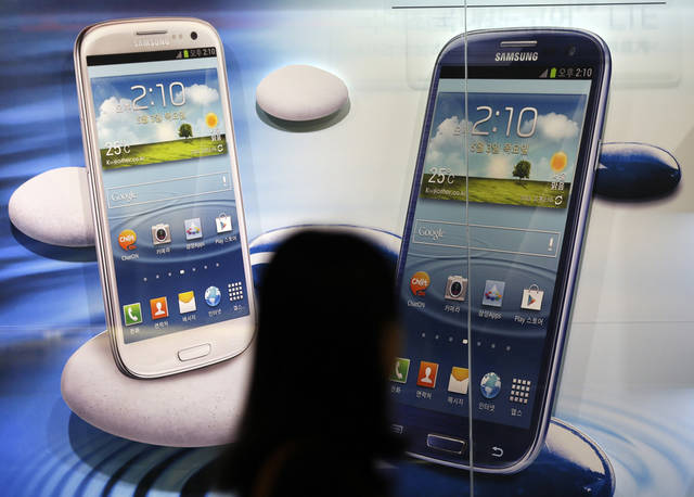 A woman walks by a billboard of Samsung Electronics's smartphones at a showroom of its headquarters in Seoul, South Korea, Friday, Oct. 5, 2012. Samsung Electronics Co. tipped all-time high quarterly operating profit, likely driven by strong sales of high-end smartphones that offset weak semiconductor orders. (AP Photo/Lee Jin-man)