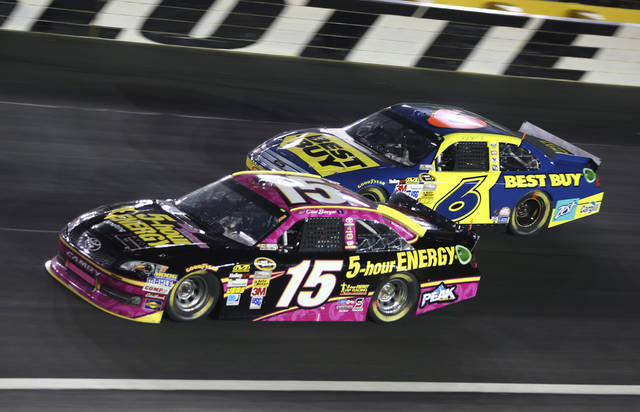 Clint Bowyer (15) races past Ricky Stenhouse Jr. (6) during the NASCAR Sprint Cup Series auto race in Concord, N.C., Saturday, Oct. 13, 2012. (AP Photo/Bob Jordan)