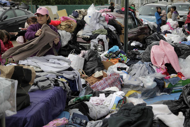 Volunteers sort through piles of donated clothes for Storm Sandy victims at an impromptu aid station in Staten Island, New York, Friday, Nov. 2, 2012.  Sandy, the storm that made landfall Monday, caused multiple fatalities, halted mass transit and cut power to more than 6 million homes and businesses. (AP Photo/Seth Wenig) ORG XMIT: NYSW131