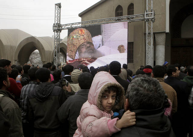 Egyptian Christians watch the funeral of the late Pope Shenouda III, on the screen, the patriarch of the Coptic Orthodox Church who led Egypt's Christian minority for 40 years during a time of increasing tensions with Muslims, at Mar Morqos, or St. Mark Coptic Orthodox Church in Cairo, Egypt, Tuesday, March 20, 2012. (AP Photo/Amr Nabil)