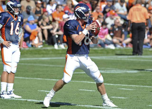 Denver Broncos quarterback Peyton Manning sets to throw as Caleb Hanie watches on Saturday morning, July 28, 2012, during the NFL football team's training camp in Engewood, Colo. (AP Photo/The Denver Post, Steve Nehf) MAGS OUT TV OUT MANDATORY CREDIT