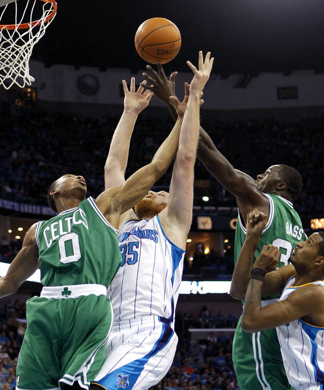 New Orleans Hornets center Chris Kaman (35) battles for a rebound between Boston Celtics shooting guard Avery Bradley (0) and power forward Brandon Bass (30) in the first half of an NBA basketball game in New Orleans, Wednesday, Dec. 28, 2011. (AP Photo/Gerald Herbert)