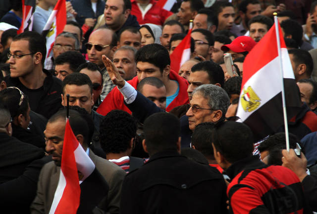Former Egyptian foreign minister Amr Moussa leads one of many anti-Morsi protest marches heading to Tahrir square Tuesday, Nov. 27, 2012. At least a hundred thousand Egyptians have been protesting today in a central square in Cairo, challenging the decision by Egypt's president to grant himself sweeping new powers. The protesters, waving Egyptian flags and chanting slogans against President Mohammed Morsi, joined hundreds of others who had been camping out in the square since Friday, demanding that the decrees be revoked. (AP Photo/Mohammed Abu Zeid)