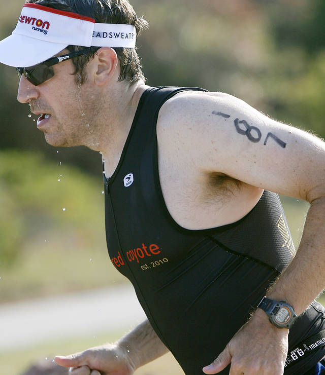 Above: Water dripps off Matt McGuire as he starts his run Sunday during the Arcadia Lake Triathlon.