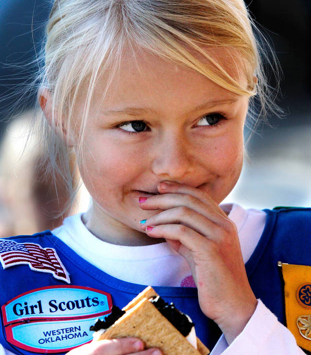 Kaci Howland, 6,  is somewhat unsure what to do with the gooey substance in her mouth after taking a bite of a s'more. She found a trash can and spit the food out.  Howland is a Daisy in Troop 625.  Edmond Girl Scouts made S'mores, a popular winter snack,  on a corner in downtown Edmond Saturday, Dec. 17, 2011, as a fundraiser for their troop.   The Scouts, with Troop 625, used a griddle as their heat source to melt marshmallows on a skewer and sandwich it with a square of chocolate between two graham crackers.  Money raised will help girls who want to join Scouts but require some financial assistance with the activity fees and various other costs involved in Scouting.  This activity was part of a series of  Downtown Edmond' Christmas celebrations.   Photo by Jim Beckel, The Oklahoman