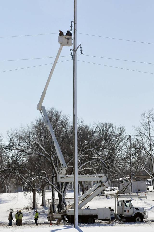 Crews work to restore power in Enid, Oklahoma Tuesday, Feb. 26, 2013. An estimated 90 % of the city was without power following the snowstorm that moved through the area Monday night and Tuesday morning. (AP Photo/ Enid News & Eagle, Billy Hefton) ORG XMIT: OKENI101