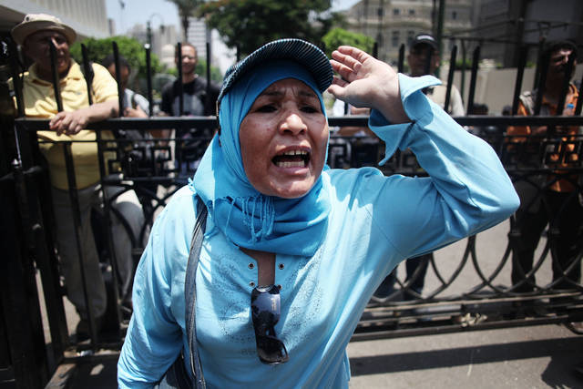 An Egyptian woman chats anti-Supreme Council for the Armed Forces (SCAF) slogans outside the Egyptian Parliament in Cairo, Egypt, Tuesday, June 19, 2012. The campaign of an Islamist who claimed victory in Egypt's presidential runoff says the Muslim Brotherhood and other political groups plan a mass demonstration later Tuesday to protest a military declaration seeking to curtail the powers of the next president. (AP Photo/Manu Brabo)