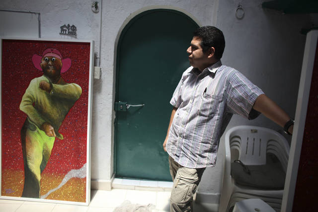 "In this photo taken June 17, 2011, painter Ricardo Delgado Herbert, 36, pauses during an interview with The Associated Press at his atelier in Mexico City. Herbert, 36, began painting a series of portraits of monster-like hit men, with crooked teeth and eyes popping out, who are holding handguns or automatic rifles. He titled it ""Glorious Pistols from the A to the Zetas,"" a reference to a drug gang, after seeing the commotion that followed a 2004 shootout between soldiers and gunmen in the border city of Matamoros. (AP Photo/Alexandre Meneghini)"