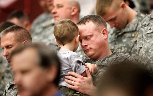 Ssgt. Arron (cq) McDaniel, of Broken Arrow, holds his 21-month-old son, Anthony, while he and fellow soldiers bow their heads for the invocation delivered by Chaplain  Maj. Brad Hanna at the 45th Infantry Brigade Combat Team deployment ceremony inside the Cox Convention Center,  Wednesday, Feb. 16, 2011.  Photo by Jim Beckel, The Oklahoman