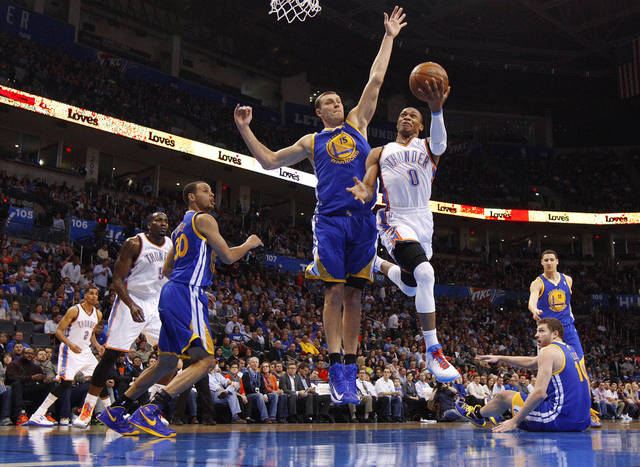 Oklahoma City's Russell Westbrook (0) goes to the basket around Golden State's Andris Biedrins (15) during an NBA basketball game between the Oklahoma City Thunder and the Golden State Warriors at Chesapeake Energy Arena in Oklahoma City, Wednesday, Feb. 6, 2013. Photo by Bryan Terry, The Oklahoman