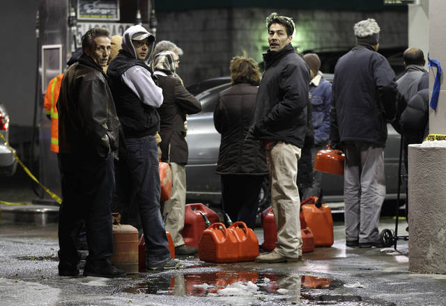 People line up with containers as they wait in line to get gas at a Hess station in the Brooklyn borough of New York where gas is still scarce, Thursday, Nov. 8, 2012. Fuel shortages and distribution delays that led to gas hoarding have prompted New York City and Long Island to initiate an even-odd gas rationing plan which begins Friday at 6 a.m. in New York and 5 a.m. in Long Island. (AP Photo/Kathy Willens)