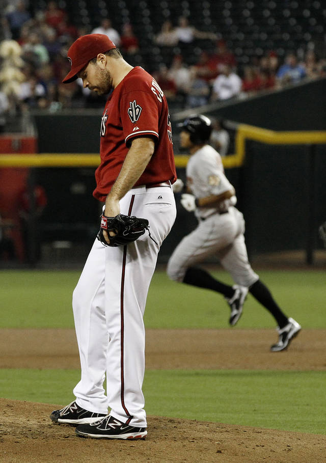 Arizona Diamondbacks' Josh Collmenter, left, kicks the pitcher's mound after giving up a home run to Houston Astros' Justin Maxwell, right, in the second inning during a baseball game on Sunday, July 22, 2012, in Phoenix. (AP Photo/Ross D. Franklin)