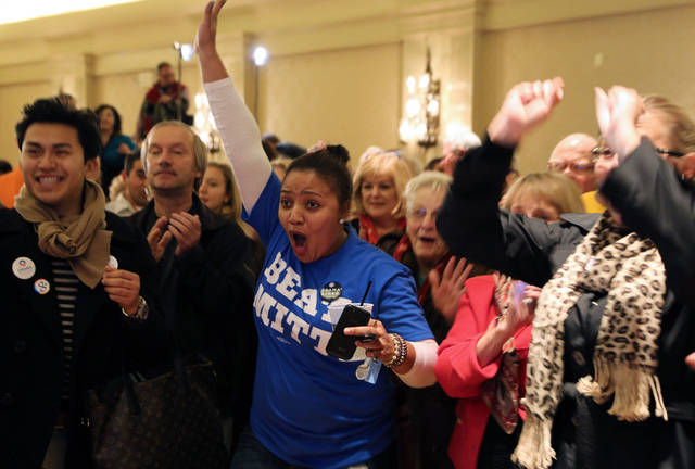 Mina Issa, center, of Des Moines, Iowa, celebrates returns in favor of President Barack Obama as winner of the election during an election night rally, Tuesday, Nov. 6, 2012, in Des Moines, Iowa. (AP Photo/Justin Hayworth)