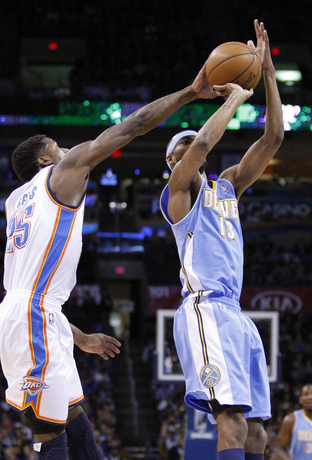 Oklahoma City Thunder guard DeAndre Liggins, left, forces the ball out of the hands of Denver Nuggets forward Corey Brewer, right, during the first quarter of an NBA basketball game in Oklahoma City, Wednesday, Jan. 16, 2013.  (AP Photo/Alonzo Adams)