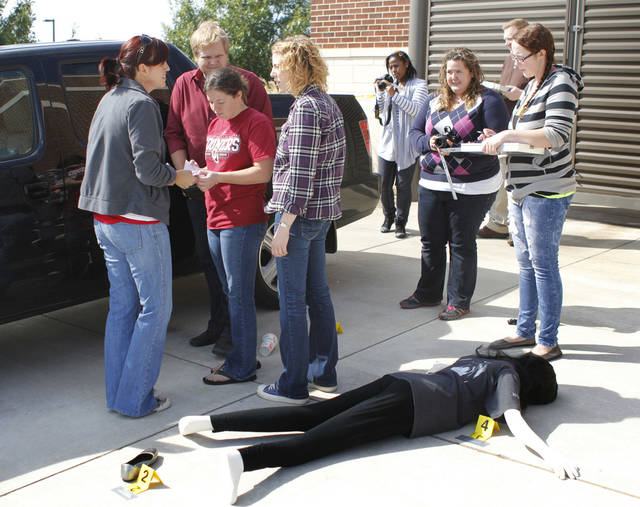 University of Central Oklahoma students discuss evidence during a crime scene processing class. In a cordoned-off area, numerical markers were placed beside a facedown victim � a mannequin � and other evidence.
