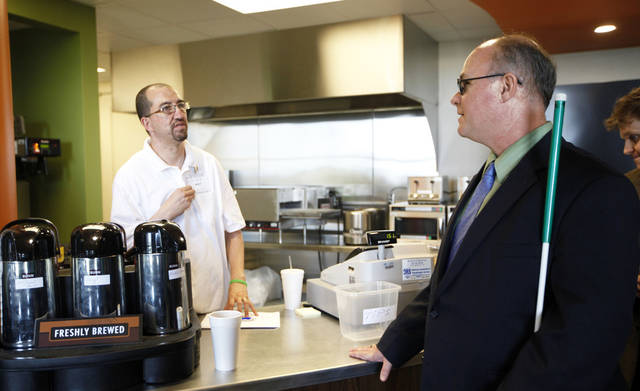 Matt Jones helps Michael Jones at a snack bar at the state Capitol. Photo by Sarah Phipps, The Oklahoman
