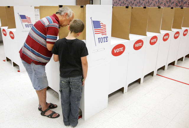 Xavier Gass, 9 from Choctaw, watches as his grandfather Jimmy R. Gass, also from Choctaw, marks his ballot in a voting booth during early voting at the Oklahoma County Election Board in Oklahoma City Monday, June 25, 2012.  Photo by Paul B. Southerland, The Oklahoman