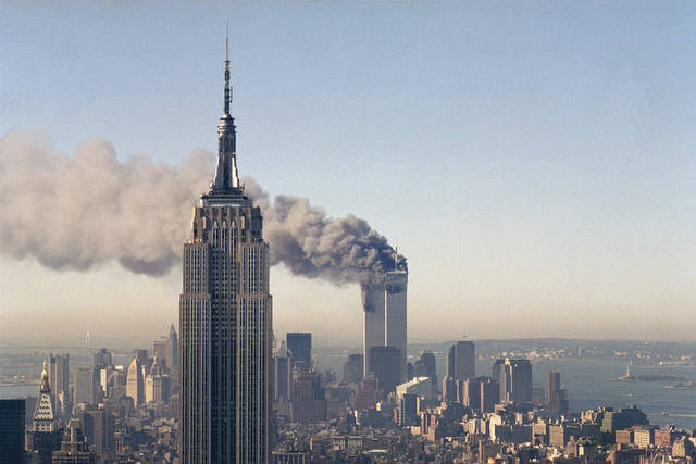 FILE - In this Sept. 11, 2001, file photo, the twin towers of the World Trade Center burn behind the Empire State Building in New York. The Sept. 11, 2001 terrorist attack is by far the most memorable moment shared by television viewers during the past 50 years, a study released on Wednesday, July 11, 2012, concluded. (AP Photo/Marty Lederhandler, File) ORG XMIT: NYET111