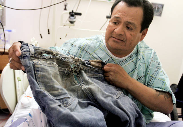 Ricky Gilmore, 49, shows the pair of pants he was wearing when he dragged himself four miles down a road for three days last week near Tocito, N.M. after a man and woman he met while he was hitchhiking left him without his wheelchair, Tuesday, Oct. 23, 2012 in Farmington, N.M. (AP Photo/The Daily Times, Augusta Liddic)