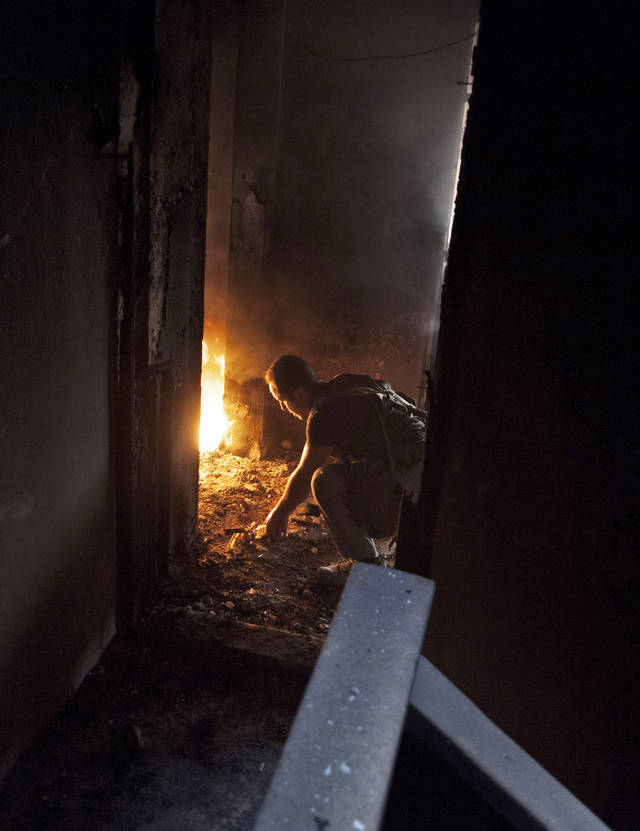   Free Syrian Army fighter is seen within a burned building during an operation against Syrian Army toops in Saif Al Dawle area in Aleppo, Syria, Wednesday, Oct. 3, 2012. Three suicide bombers detonated cars packed with explosives in a government-controlled area of the battleground Syrian city of Aleppo on Wednesday, killing at least 34 people, leveling buildings and trapping survivors under the rubble, state TV said. More than 120 people were injured, the government said. (AP Photo / Manu Brabo)  
