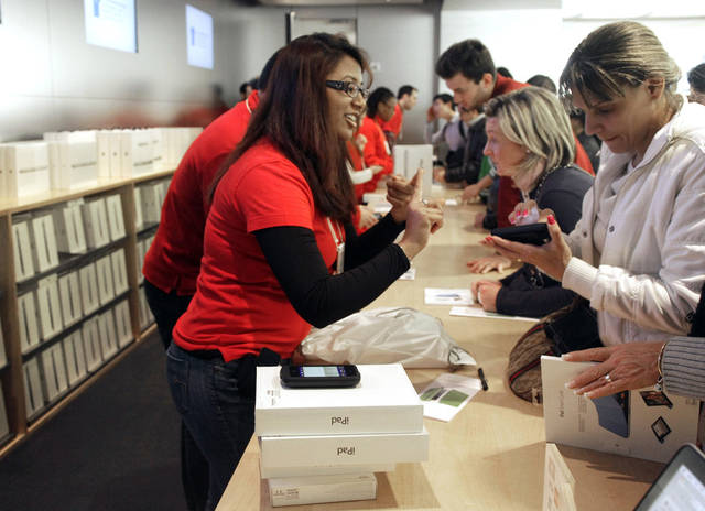 A shopper at Apple's flagship store in New York, buys two iPads, Friday, Nov. 23, 2012. Black Friday, the day when retailers traditionally turn a profit for the year, got a jump start this year as many stores opened just as families were finishing up Thanksgiving dinner. (AP Photo/Richard Drew)