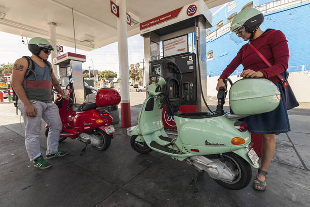   Motorcyclists Hanna Gilan, right, and her son Chaim Gilan fill up their Vespas scooters with less than two gallons at a gas station in the Echo Park district of Los Angeles Thursday, Oct. 4, 2012. Motorists in California paid an average of $4.232 per gallon Wednesday. That&acirc;s 45 cents higher than the national average and exceeded only by Hawaii among the 50 states. (AP Photo/Damian Dovarganes)  