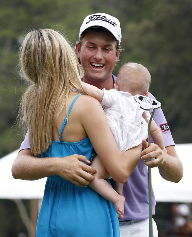 FILE - This Aug. 21, 2011 file photo shows Webb Simpson, center, embracing his wife, Dowd, and son James, after winning the Wyndham Championship golf tournament in Greensboro, N.C. The Raleigh native and U.S. Open champion's star has rocketed in the 12 months since he claimed his first PGA Tour title at the Wyndham Championship. (AP Photo/Chuck Burton, File)