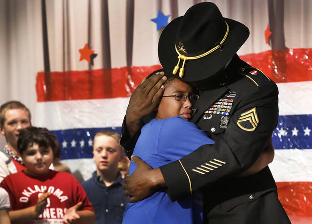 Staff Sergeant Harold Williams surprised his son, Adrian, a fifth grade student during a patriotic-themed Veteran&#039;s Day assembly Friday morning, Nov. 9, 2012, at Schwartz Elementary School, when he walked onto the stage while his son and classmates were reciting the preamble of the U.S. Constitution.  The elder Williams arrived at the school this morning and had been hidden off stage until his son&#039;s class gathered on the stage. Father and son embraced for nearly two minutes in front of a large red, white and blue backdrop. Adrian wiped away tears and tears also rolled down the cheeks of Sgt. Williams.  Harold has been stationed in Germany with the U.S. Army and recently returned there from duty in Iraq.      Photo by Jim Beckel, The Oklahoman