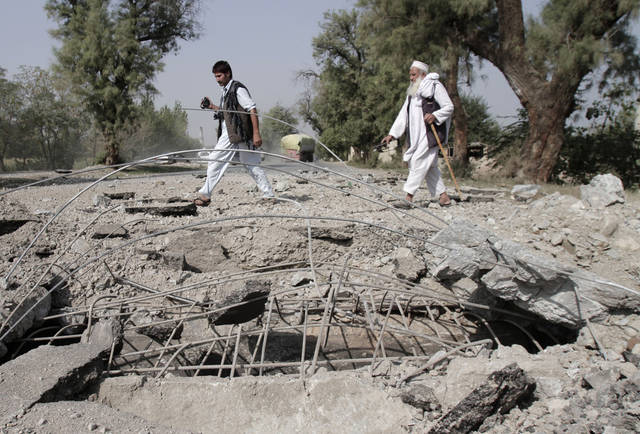 Afghan men walk past a damaged road after a bomb exploded in the Batikot district of Jalalabad, east of Kabul, Afghanistan, Tuesday Oct. 9, 2012. A roadside bomb hit a civilian car in Batikot district of Jalalabad province injuring several civilians, according to Jalalabad provincial spokesman Ahmad Zia Abdulzai. (AP Photo/Rahmat Gul)