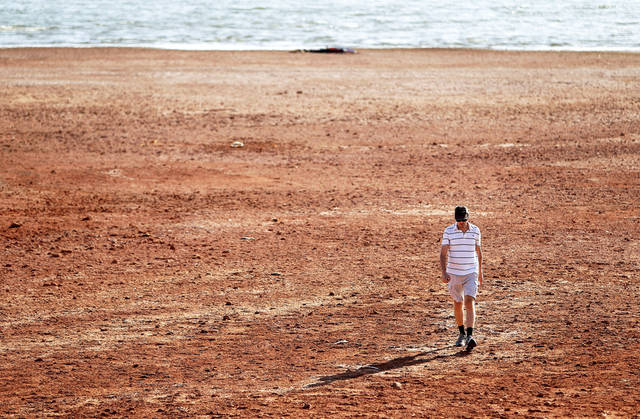 Paul Gilchrest, of Oklahoma City, walks across the receding shoreline of Lake Hefner recently. Oklahoma City has experienced record heat and drought this summer, similar to conditions in the city in the summer of 1936. PHOTO BY BRYAN TERRY, THE OKLAHOMAN