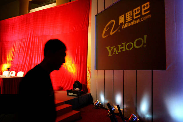 FILE - In this Aug. 11, 2005, file photo, a man walks past a screen displaying the Yahoo and Ali Baba.com logos before a joint news conference by the companies at the China World hotel in Beijing. Yahoo announced that it has agreed to sell half of its 40 percent stake in Chinese e-commerce company Alibaba for about $7.1 billion. The deal will see Alibaba Group buying back the stake from Yahoo Inc. for $6.3 billion cash and up to $800 million of Alibaba preference shares. (AP Photo/Elizabeth Dalziel, File)
