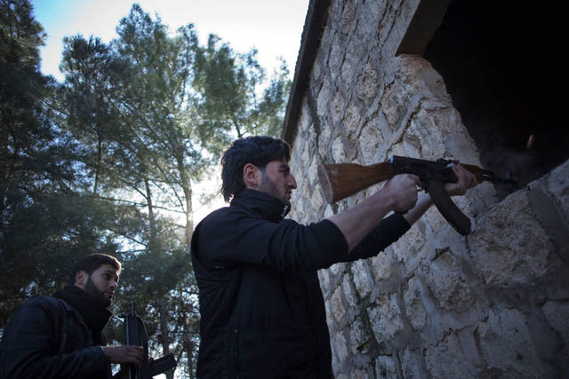 A Free Syrian Army fighter fires his machine gun toward Syrian Army positions during an assault on a military base in Tal Sheen, Syria, Saturday, Dec 15, 2012 (AP Photo / Manu Brabo)