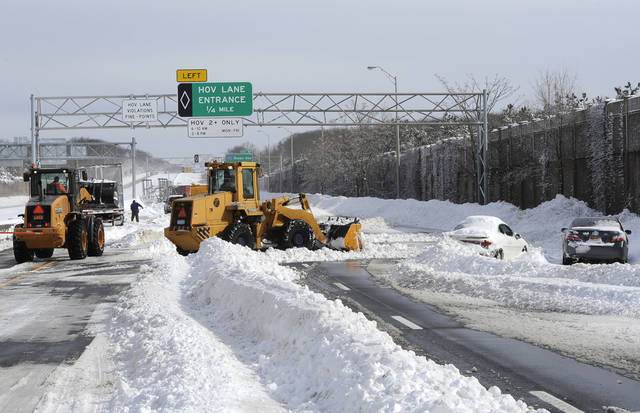 Payloaders clear snow from the Long Island Expressway just west of exit 59 Ocean Ave where several cars are abandoned after a snow storm on Saturday, Feb. 9, 31, 2013, in Ronkonkoma , N.Y. (AP Photo/Kathy Kmonicek)