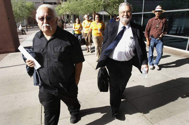Salvador Reza, left and Rev. Peter Morales walk into Maricopa County Justice Court Friday, July 29, 2011, in Phoenix, for their trail on civil disobedience charges. They and more than 80 others were arrested for blocking the entrance of the Maricopa County jail in downtown Phoenix as they protested Arizona's immigration law SB1070 last year. (AP Photo/Ross D. Franklin)