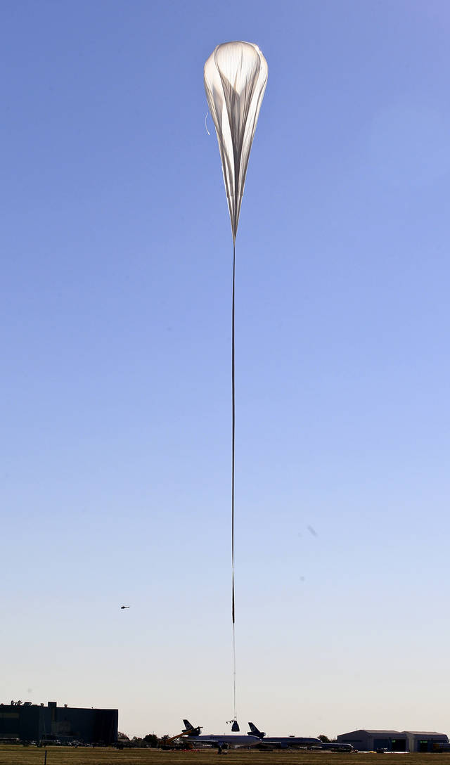 The capsule and attached helium balloon carrying Felix Baumgartner  just leaves the ground as it lifts off as he attempts to break the speed of sound with his own body by jumping from a space capsule lifted by a helium balloon, Sunday, Oct. 14, 2012, in Roswell, N.M.  Baumgartner plans to jump from an altitude of 120,000 feet, an altitude chosen to enable him to achieve Mach 1 in free fall, which would deliver scientific data to the aerospace community about human survival from high altitudes.(AP Photo/Ross D. Franklin) ORG XMIT: NMRF107