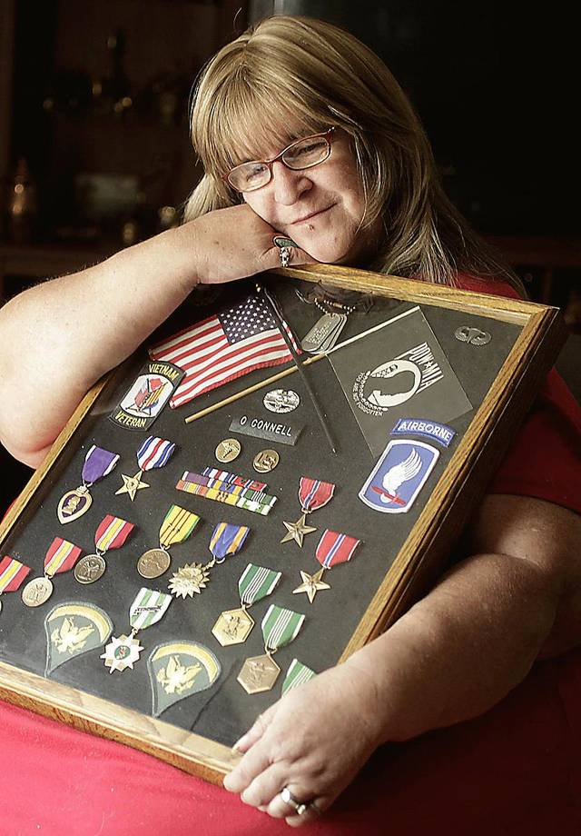 Kathy O'Connell poses with medals her late husband, Larry O'Connell, was awarded for his actions in the Vietnam War. Photo by MIKE SIMONS, TULSA WORLD