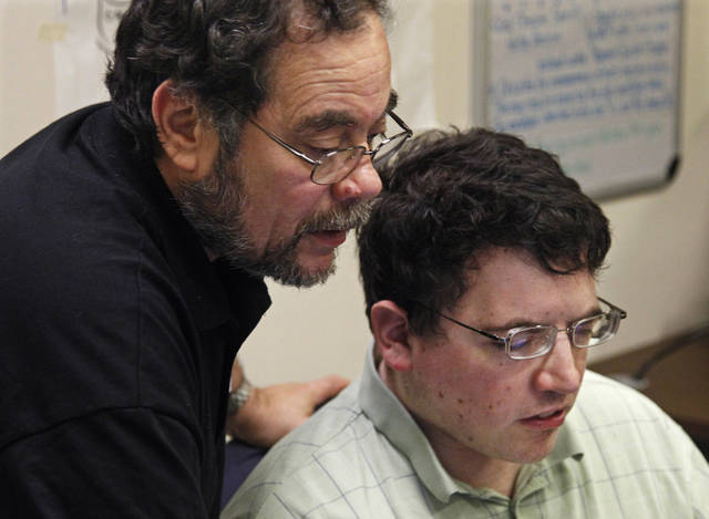 In this photo taken Thursday, Sept. 8, 2011, Aspiritech co-founder Moshe Weitzberg works with his son, Oran, an employee at the nonprofit enterprise that specializes in finding software bugs, as they test a new program in Highland Park, Ill. Aspiritech hires only people with autism disorders. Traits that make great software testers _intense focus, comfort with repetition, memory for detail _ also happen to be characteristics of autism. (AP Photo/M. Spencer Green)