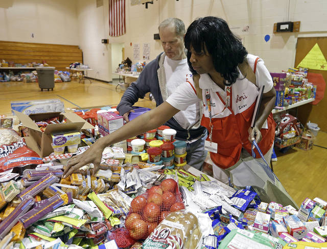 Red Cross worker Lori Burts helps Dan Able with food items at a shelter set-up for the victims whose homes were damaged by the house explosion, Sunday, Nov. 11, 2012, in Indianapolis. Nearly three dozen homes were damaged or destroyed, and seven people were taken to a hospital with injuries, authorities said Sunday. The powerful nighttime blast shattered windows, crumpled walls and could be felt at least three miles away. (AP Photo/Darron Cummings)