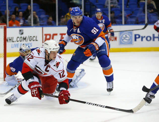 Carolina Hurricanes center Eric Staal (12) passes the puck out to a teammate in front of New York Islanders center John Tavares (91) during the first period of an NHL hockey game at the Nassau Coliseum in Uniondale, N.Y., Monday, Feb.11, 2013. (AP Photo/Paul J. Bereswill)