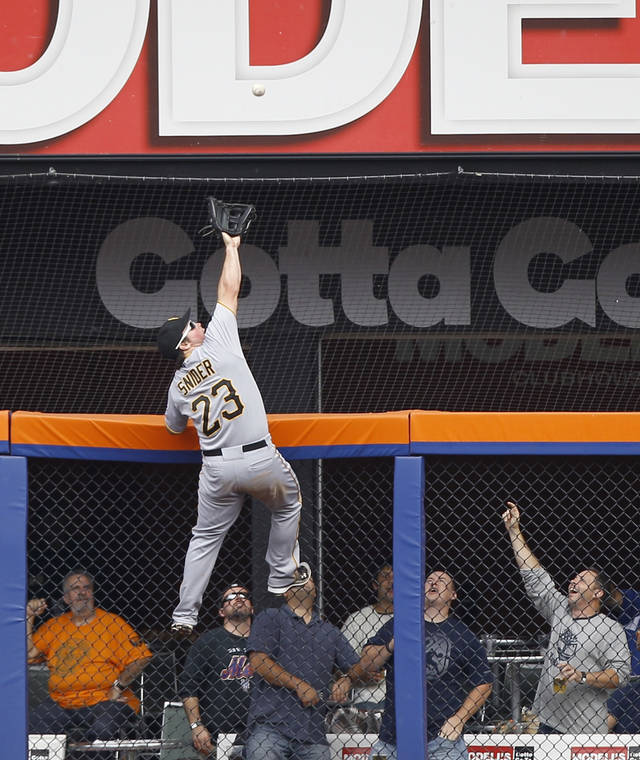 Pittsburgh Pirates right fielder Travis Snider climbs the fence to rob New York Mets' Mike Baxter of a home run during the second inning of a their baseball game at Citi Field in New York, Thursday, Sept. 27, 2012. (AP Photo/Kathy Willens)